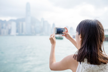 Woman taking photo of the skyline in Hong Kong