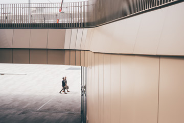 Architectural view of two businessman walking and chatting Fotoväggar