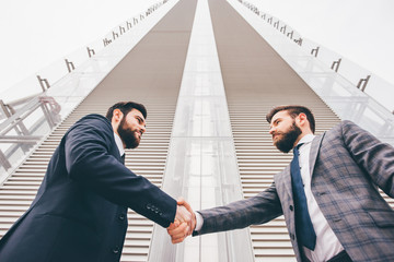 Business handshake in front of high office building