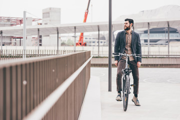 young casual bearded businessman riding bike