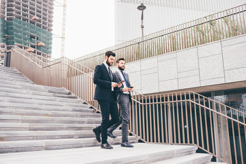 Two contemporary businessman walking downstairs using devices