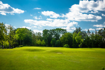 Pictire of amazing and astonishing golf course landscape with blue sky and white clouds. Beautiful nature and environment.
