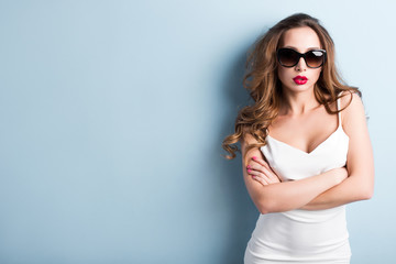 Young woman in sunglasses in the studio.