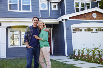 Portrait Of Couple Standing Outside House