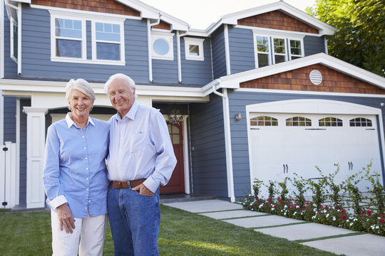 Portrait Of Senior Couple Standing Outside House
