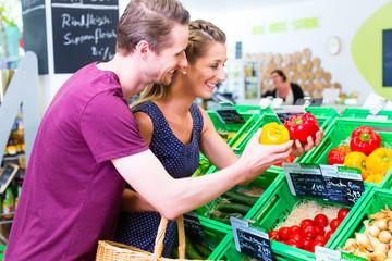 Paar wählt Paprika einer Gemüseabteilung im Bio Supermarkt aus