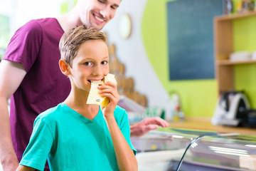 Vater und Sohn wählen Käse an der Bio Supermarkt Käsetheke
