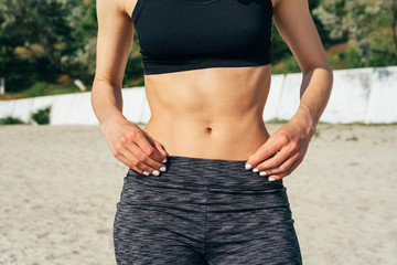 Close-up of sporty girl with a flat belly on the beach