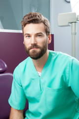Portrait of serious young handsome attractive male doctor with beard in green costume sitting in dental clinic. Face expressions, emotion, healthcare, medicine.