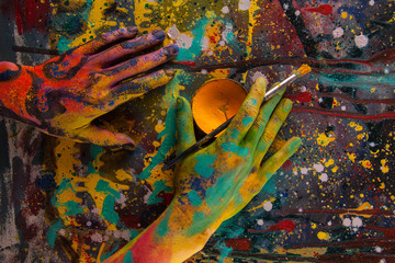 Hand hold paint bottle. Hands in paint. Woman painter. Colorful background.