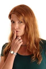 Frau hält Zeigefinger an den Mund und fordert zum Schweigen auf