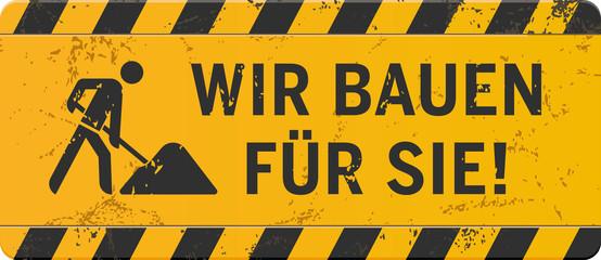 gelbes Schild Wir bauen für Sie mit Bauarbeiter-Icon zerkratzt
