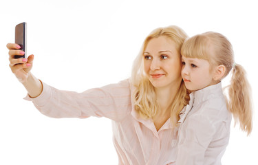 Happy mother and daughter taking selfie over wall