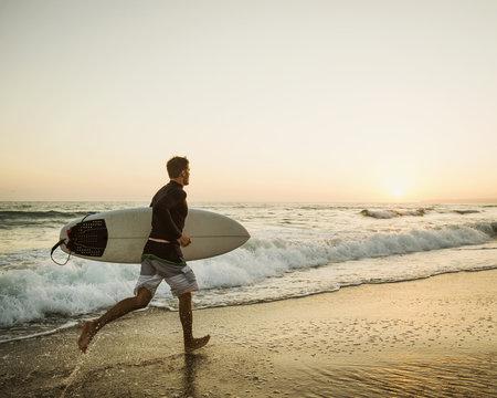Caucasian man carrying surfboard on beach