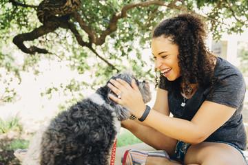 Black woman petting dog outdoors