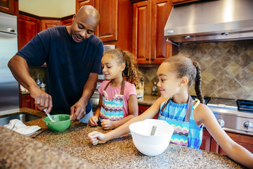 Father and daughters cooking in kitchen