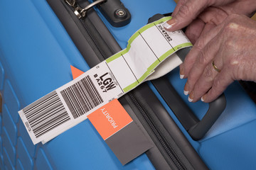 PRIORITY TAG ON A BLUE SUITCASE - MAY 2016 - Airline priority tag being secured to a blue suitcase