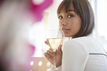 Mixed race woman drinking white wine