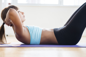 Mixed race woman doing sit-ups on yoga mat