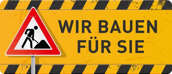 gelbes Schild Wir bauen für Sie mit Bauarbeiter-Schild