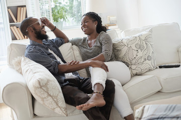 Black couple talking on sofa