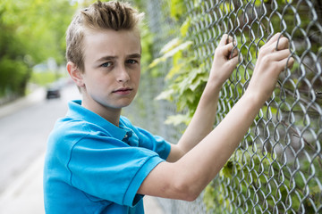 young teen boy looking out of a fence