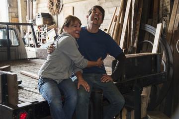 Caucasian workers hugging in truck bed