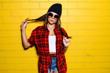 Beautiful young sexy hipster girl posing and smiling near urban yellow wall background in sunglasses, red plaid shirt, shorts, hat.