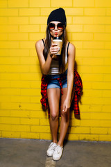Beautiful young sexy hipster girl drink coffee, smiling and posing near urban yellow wall background in sunglasses, red plaid shirt, shorts, hat.