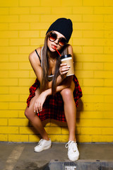 Beautiful young sexy hipster girl drink coffee and sitting near urban yellow wall background in sunglasses, red plaid shirt, shorts, hat.