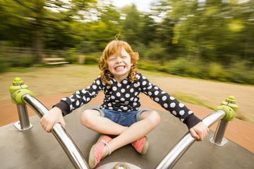 Caucasian girl playing on merry-go-round