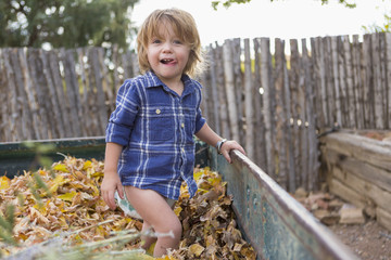 Caucasian boy standing in autumn leaves