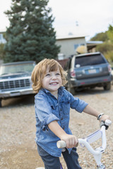 Caucasian boy riding tricycle in gravel