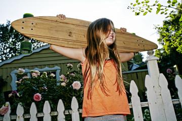Caucasian girl carrying skateboard outdoors