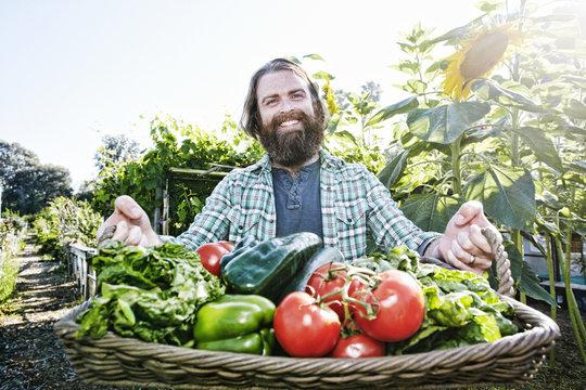 Caucasian man holding basket of vegetables in garden
