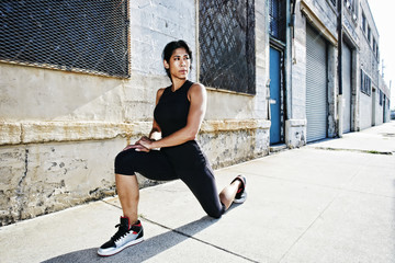 Mixed race woman stretching on sidewalk