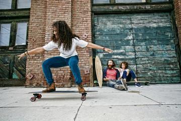 Family riding skateboards on sidewalk