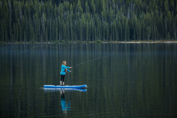 Caucasian woman fishing from paddle board in river