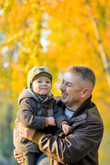 Father playing with his son in the park in autumn.