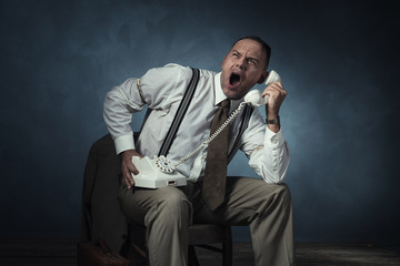 Screaming angry retro 1940 man on the phone sitting on chair in