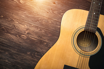 Acoustic guitar resting against a wooden background with copy sp