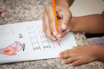 Mother's hand holding child hand writing her homework