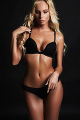 Blonde sexy woman in black lingerie.sexual beautiful girl in underwear. perfect tan