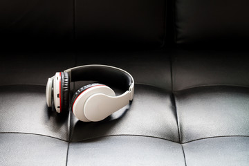Bluetooth headphones on black leather background