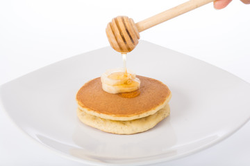 honey dripping on the cake and banana in plate