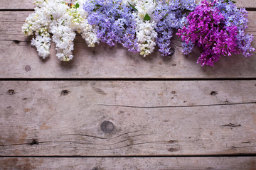Border from fresh aromatic lilac flowers on vintage wooden plank