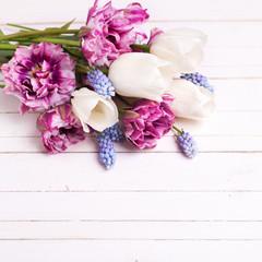 Fresh spring flowers on white wooden table.