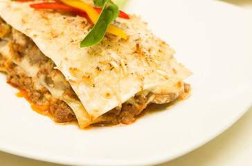 Closeup delicious lasagne serving sitting on white plate, catering concept
