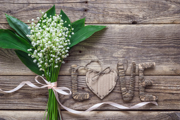 Background with bouquet of  lily of the valley and cardboard let