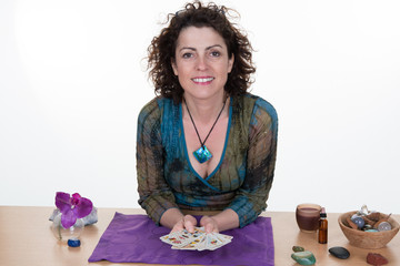 Female Fortuneteller laying Tarot cards on purple